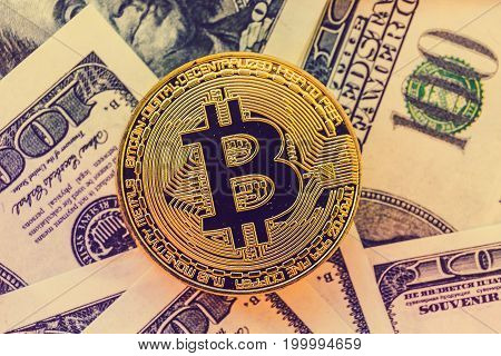 Gold Bitcoin on US dollars background, toned