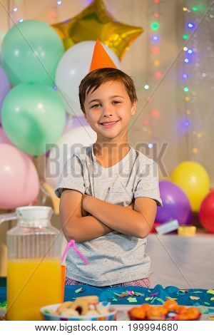 Portrait of cute boy standing with arms crossed at birthday party