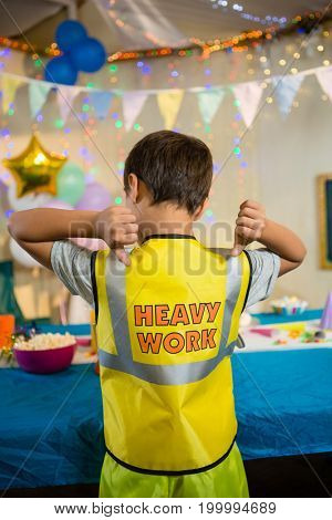 Rear view of boy gesturing to the text on protective workwear