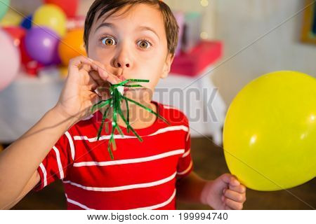 Cute boy blowing party horn during birthday party at home