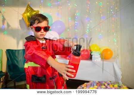 Cute boy pretending to be a fireman during birthday party at home