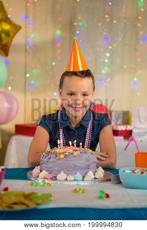 Portrait of girl standing with birthday cake at home