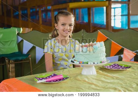Portrait of girl sitting near a birthday cake at home
