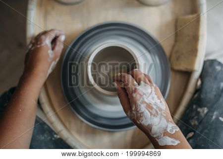 Top view of dirty potter woman hands works at pottery wheel, potter makes new ceramic production, selective focus, toned