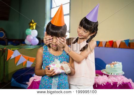 Smiling girl covering birthday girls eyes and offering a gift