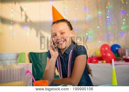 Girl talking on mobile phone during birthday party at home