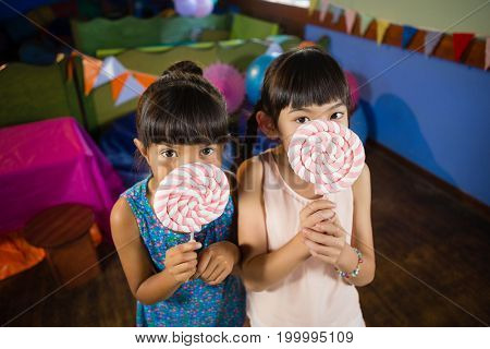 Portrait of kids holding a lollipop during birthday party at home
