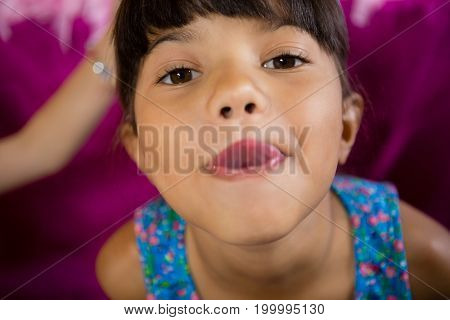 Portrait of girl making funny faces during birthday party at home