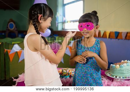 Kids interacting with each other during birthday party at home