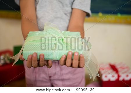 Mid-section of boy holding a gift box during birthday party at home