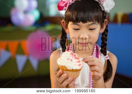Cute girl decorating cupcake during birthday party at home
