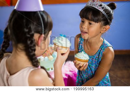 Kids having cupcake during birthday party at home