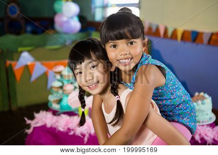 Girl giving piggyback ride to her friend during birthday party at home