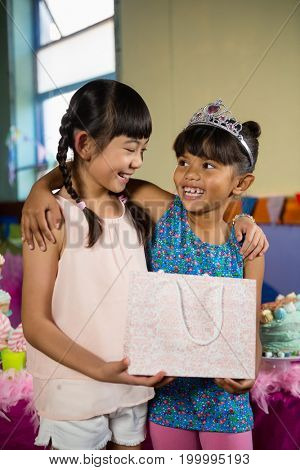 Kids holding gift bag during birthday party at home