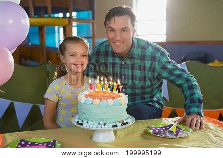 Portrait of father and daughter celebrating birthday at home