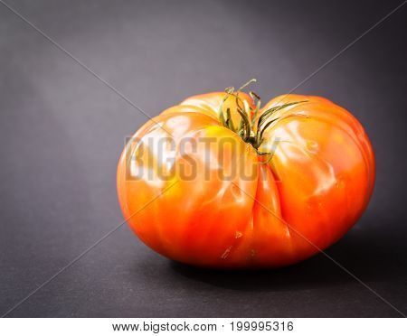 Ripe Heirloom Tomato Isolated On Black Back Ground. The tomato is red and ready to be eaten.