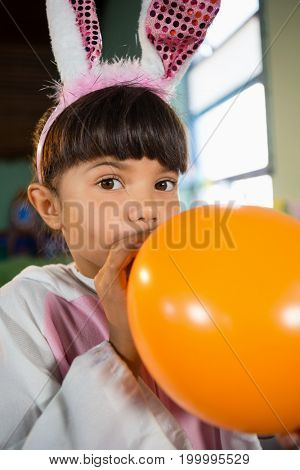 Portrait of girl blowing balloon during birthday party at home