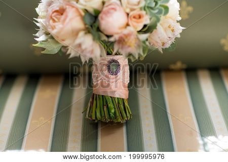 Elegant wedding flower bouqet on texture green sofa background close-up