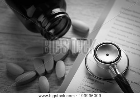 stethoscope and yellow pills with document concept healthcare