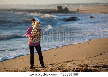 Musician play to Tuba on romantic sea shore.