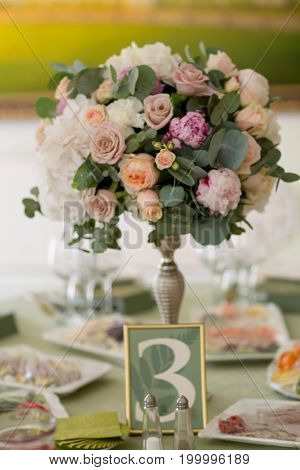 Table with flowers set for an event party or wedding reception, green theme