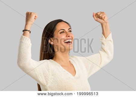 Studio shot of a happy young woman with arms raised