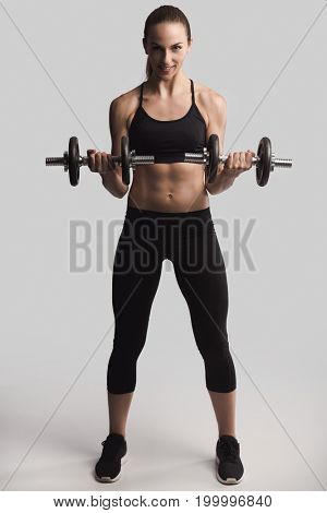 Beautiful young woman in a workout gear lifting dumbbells