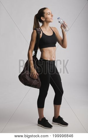 Portrait of sporty young posing with a gym bag and drinking water