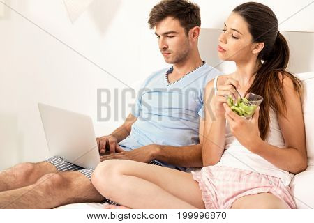 Addicted young man on bed with a laptop while the woman looks angry
