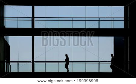Silhouette view of two people in a modern office building interior with panoramic windows.