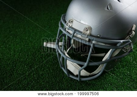 Close-up of American football head gear over artificial turf