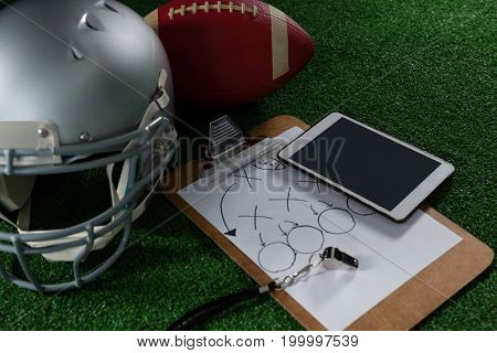 Close-up of American football head gear, tablet, whistle and football on artificial turf