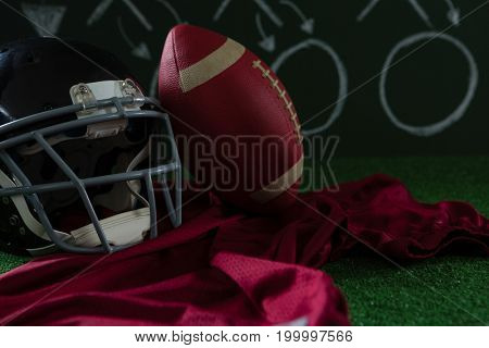Close-up of American football jersey, head gear and football lying on artificial turf against strategy board