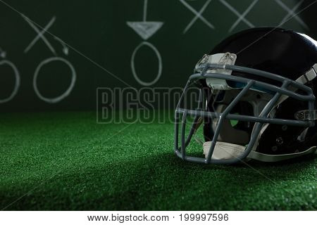 Close-up of American football head gear lying on artificial turf against strategy board