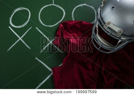 Close-up of American football jersey and head gear lying on green board with strategy drawn on it