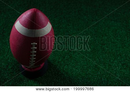 Close-up of American football standing on holder on artificial turf against black background
