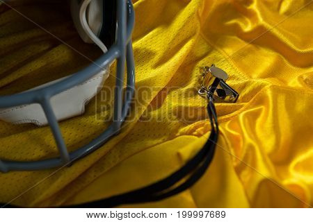 Close-up of American football jersey, referee whistle and head gear