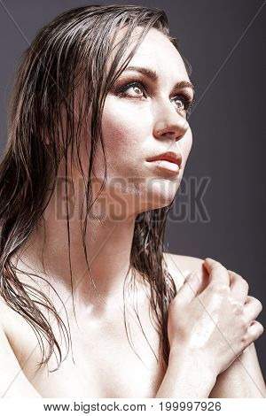 Beauty Concepts. Portrait of Sensual Tanned Caucasian Brunette Woman Looking Up with Wet and Shining Skin and Wet Hair. Against Dark Grey Background. Vertical Image