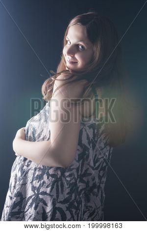 Happy smiling Caucasian Brunette Pregnant Woman Posing Against Black. Vertical Image Composition