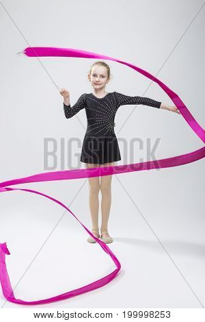 Portrait of Caucasian Female Rhythmic Gymnast In Professional Competitive Black Sparkling Starry Suit Doing Artistic Ribbon Spirals Exercises in Studio On White. Vertical Image Composition