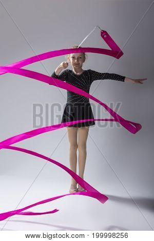 High Contrsat Portrait of Caucasian Female Rhythmic Gymnast In Professional Competitive Black Sparkling Starry Suit Doing Artistic Ribbon Spirals Exercises in Studio. Vertical Image