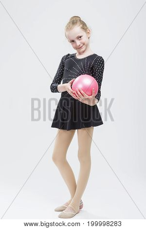 Full Length Portrait of Caucasian Female Rhythmic Gymnast In Professional Competitive Black Sparkling Suit Posing With Ball in Studio On White. Vertical Image