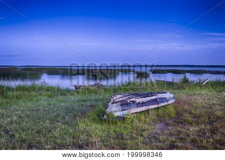 Scenic Destinations. Turned Over Boat on The Ground Near Water Surface in Belarussian National Park Braslav Lakes at Sunset during Summer Time.Horizontal Composition