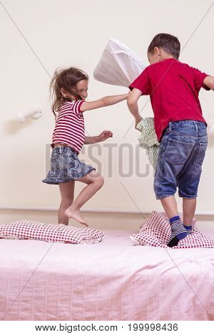 Funny Kids Playing with Pillows on Bedroom. Improvised Children Battel Indoors.Vertical Image