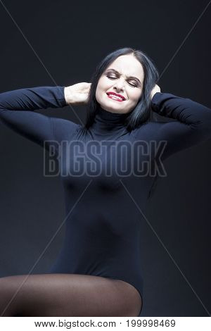 Portrait of Screaming Caucasian Mature Brunette. Posing in Black Body suit Against Black.Vertical Image Orientation