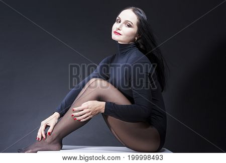 Portrait of Smiling Sexy and Alluring Caucasian Mature Brunette Woman in Black Body Suit. Posing Against Black Background. Horizontal Composition