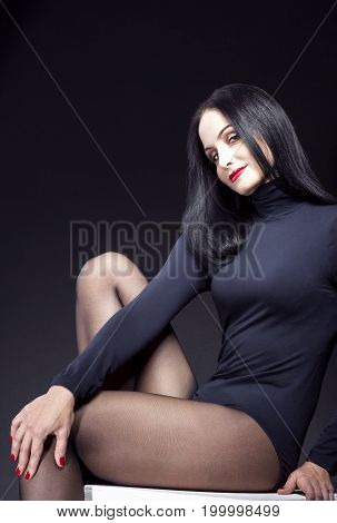 Natural Portrait of Sensual Caucasian Brunette Posing in Black Body Suit on White Prop. Demonstrating Attractive Sexy Legs. Against Black Background. Vertical Image Orientation