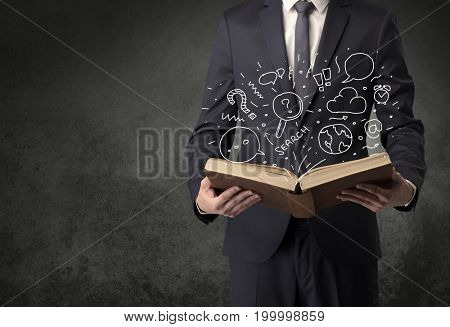 Businessman holding book with doodle drawings and signs.
