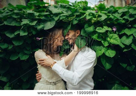 portrait of beautiful wedding couple hugging near green bushes