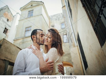 full length of couple posing near church in old town